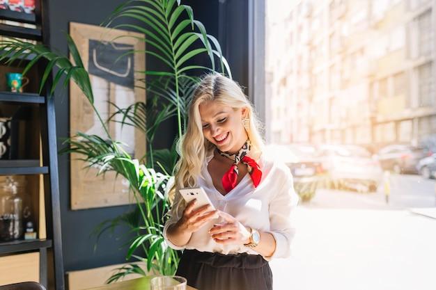 Giovane donna sorridente alla moda che sta vicino alla finestra facendo uso del telefono cellulare