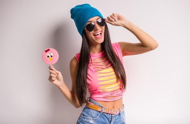 Giovane donna sorridente alla moda in protezione blu ed occhiali da sole.
