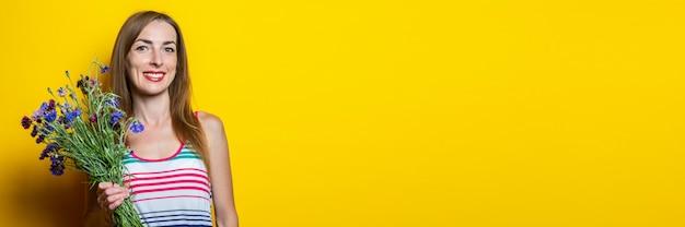 Giovane donna sorridente allegra in un vestito a strisce con un mazzo di fiori