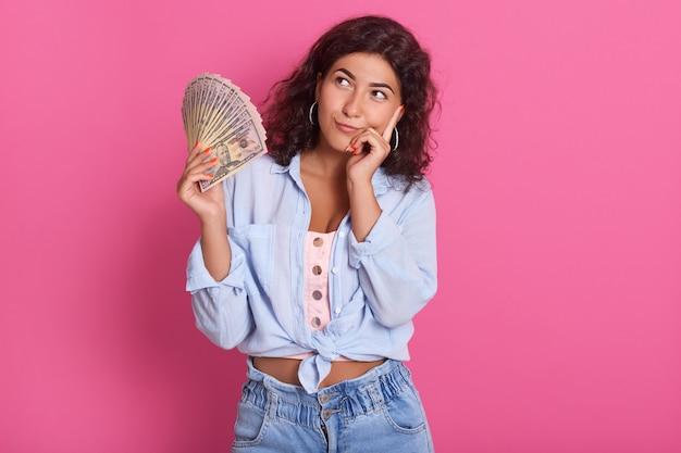 Giovane donna sorridente attraente che pensa a come spendere il suo mazzo di soldi, femmina che porta camicia e jeans blu, stanti contro la parete rosa con l'espressione pensierosa.