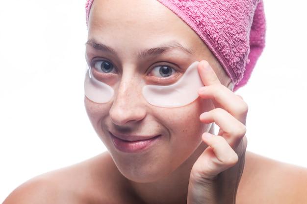 Giovane donna sorridente attraente con le toppe bianche sotto gli occhi e un asciugamano rosa sulla sua testa isolata su bianco. ritratto del primo piano cura della pelle