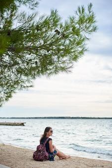 Giovane donna sorridente attraente con lo zaino variopinto che si siede da solo sulla spiaggia sabbiosa dell'oceano su chiari acqua e cielo blu luminosi