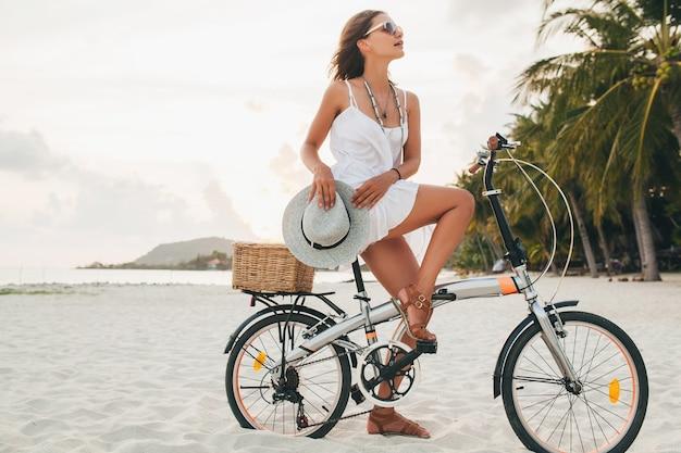 Giovane donna sorridente attraente in vestito bianco che guida sulla spiaggia tropicale in bicicletta che indossa cappello e occhiali da sole