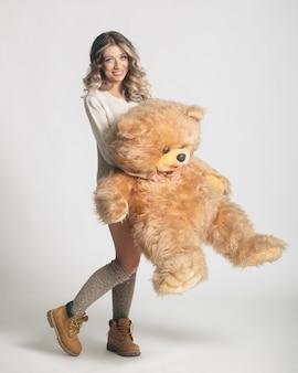 Giovane donna sorridente casuale in vestiti tricottati che tengono grande orsacchiotto molle