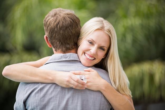 Giovane donna sorridente che abbraccia uomo