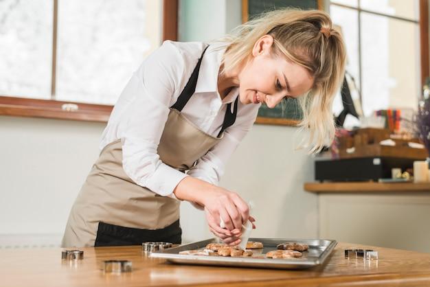 Giovane donna sorridente che applica crema sopra i biscotti cotti sul vassoio di cottura