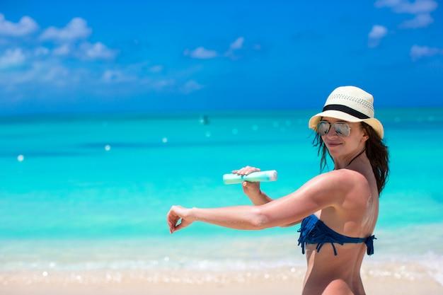 Giovane donna sorridente che applica la crema del sole sulla spiaggia