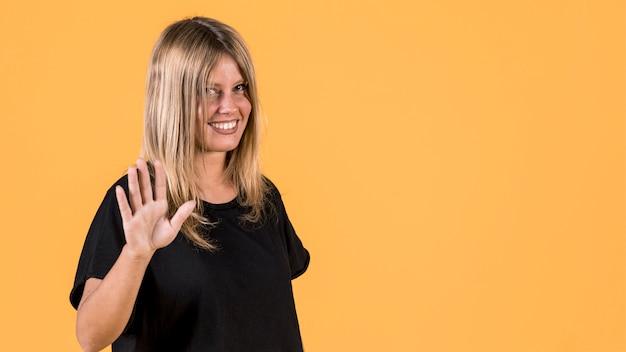 Giovane donna sorridente che controlla contesto giallo