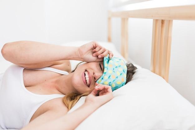 Giovane donna sorridente che dorme sul letto con una maschera per gli occhi