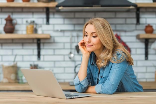 Giovane donna sorridente che esamina computer portatile sulla tavola nella cucina