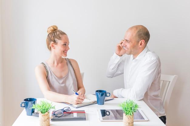 Giovane donna sorridente che esamina uomo che parla sul cellulare nel luogo di lavoro