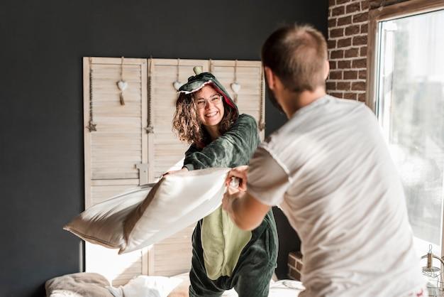 Giovane donna sorridente che fa lotta di cuscino con il suo marito a casa