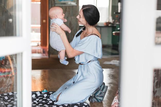 Giovane donna sorridente che gioca con il suo bambino a casa