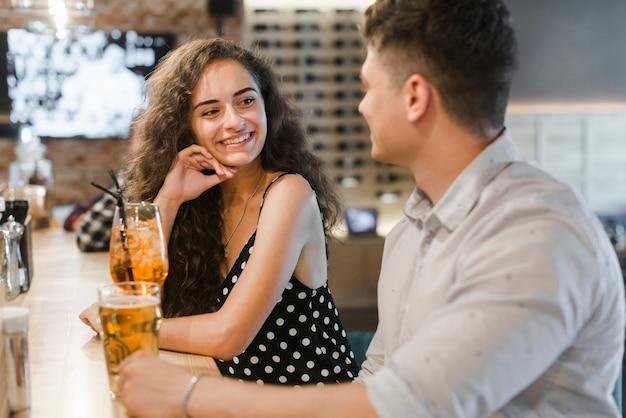 Giovane donna sorridente che gode della bevanda con il suo ragazzo