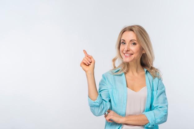 Giovane donna sorridente che indica la sua barretta contro la priorità bassa bianca