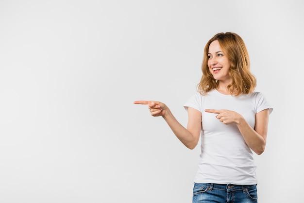 Giovane donna sorridente che indica le dita contro la priorità bassa bianca