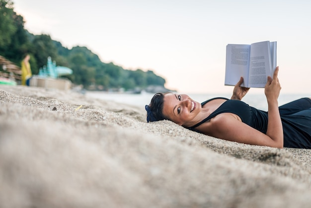 Giovane donna sorridente che legge un libro sulla spiaggia. copia spazio
