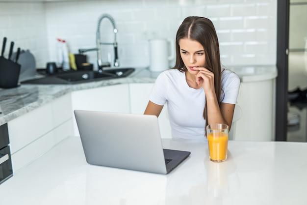 Giovane donna sorridente che mangia prima colazione nella cucina che si collega con un computer portatile e che beve un succo d'arancia sano