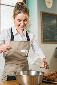 Giovane donna sorridente che mette crema bianca nel sacchetto di glassa bianco