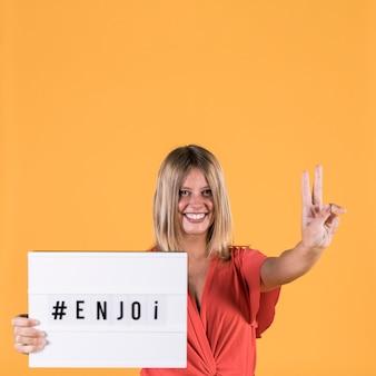 Giovane donna sorridente che mostra il segno di pace mentre tenendo scatola leggera con testo