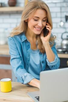 Giovane donna sorridente che per mezzo del computer portatile che parla sullo smart phone