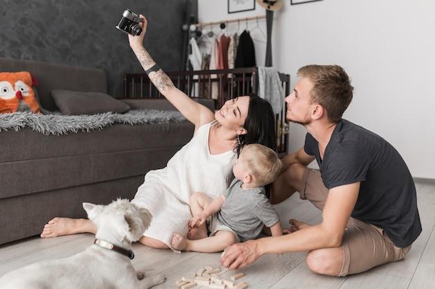 Giovane donna sorridente che prende selfie della sua famiglia mentre sedendosi nel salone