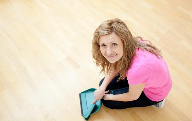 Giovane donna sorridente che pulisce il pavimento