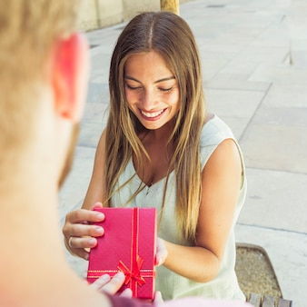 Giovane donna sorridente che riceve il regalo del biglietto di s. valentino