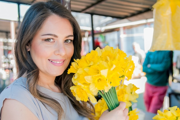 Giovane donna sorridente che seleziona fiori freschi. primo piano profilo ritratto di una bella e giovane donna godendo e sentire l'odore di un mazzo di fiori, mentre in piedi in una fresca stalla di mercato floreale durante una giornata di sole all'aperto.