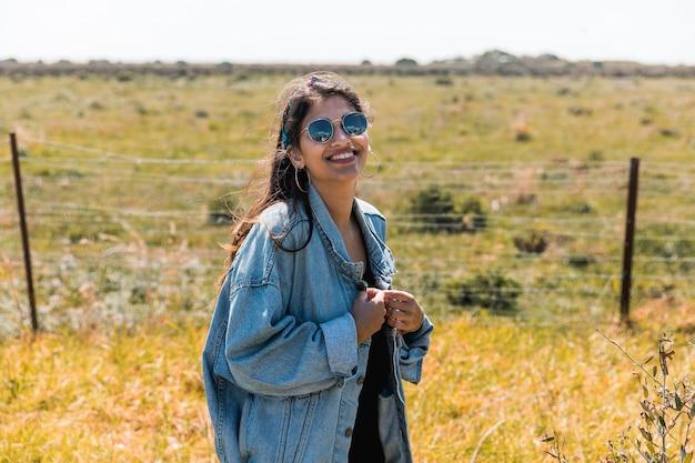 Giovane donna sorridente che si leva in piedi in natura