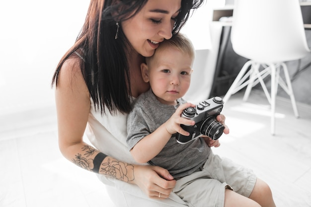Giovane donna sorridente che si siede con la sua macchina fotografica della tenuta del figlio a casa
