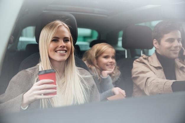 Giovane donna sorridente che si siede in automobile con la famiglia