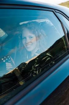 Giovane donna sorridente che si siede in macchina