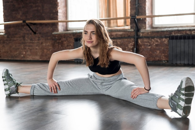 Giovane donna sorridente che si siede sul pavimento che allunga la sua parte del piedino