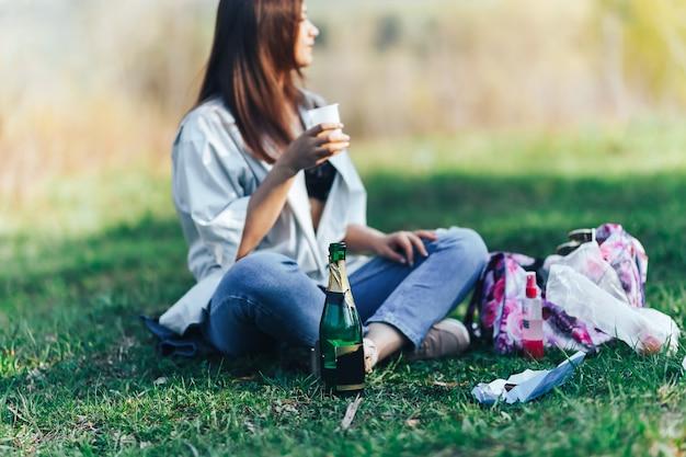 Giovane donna sorridente che si siede sull'erba e che beve vino
