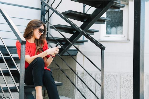 Giovane donna sorridente che si siede sulla scala per mezzo del cellulare