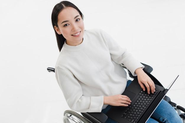 Giovane donna sorridente che si siede sulla sedia a rotelle facendo uso del computer portatile contro fondo bianco