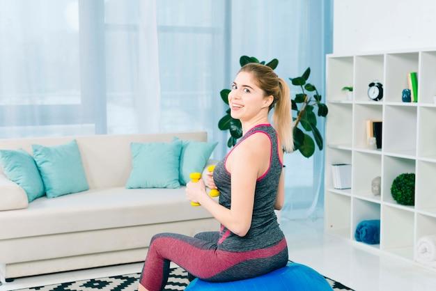 Giovane donna sorridente che si siede sulla sfera di forma fisica che si esercita con i dumbbells gialli
