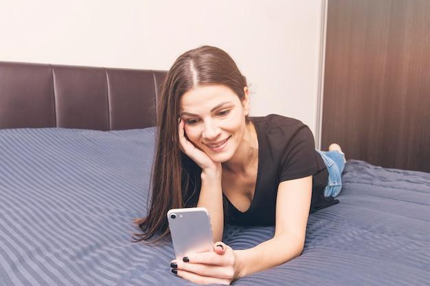 Giovane donna sorridente che si trova sul letto facendo uso del telefono cellulare