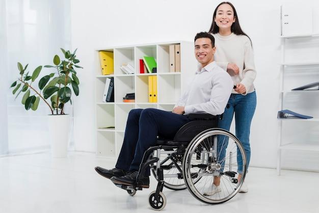 Giovane donna sorridente che sta dietro l'uomo d'affari che si siede sulla sedia a rotelle