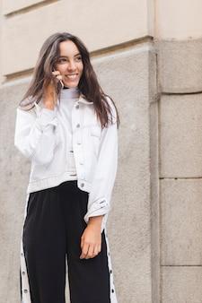 Giovane donna sorridente che sta fuori che parla sul telefono cellulare