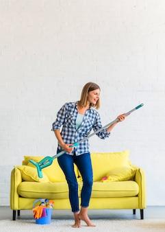 Giovane donna sorridente che sta sul tappeto che balla con la zazzera