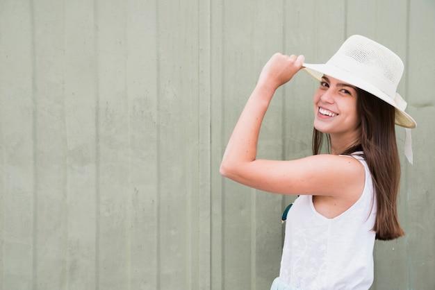 Giovane donna sorridente che sta vicino al recinto di legno
