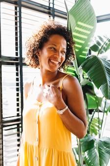 Giovane donna sorridente che sta vicino alla finestra al sole