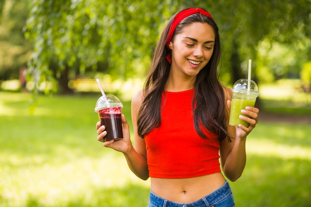 Giovane donna sorridente che tiene i frullati verdi e rossi in tazza di plastica