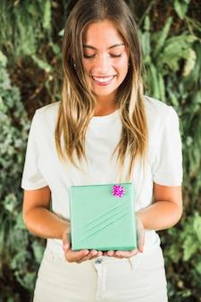 Giovane donna sorridente che tiene il contenitore di regalo verde