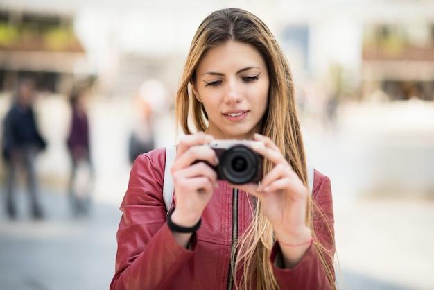 Giovane donna sorridente che tiene una macchina fotografica
