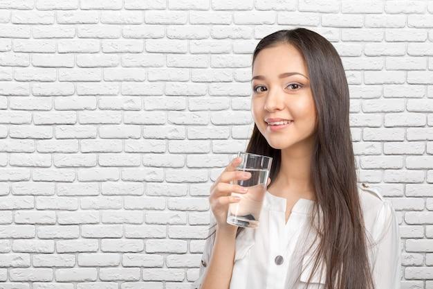 Giovane donna sorridente con bicchiere d'acqua