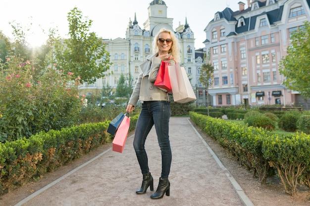 Giovane donna sorridente con borse per lo shopping