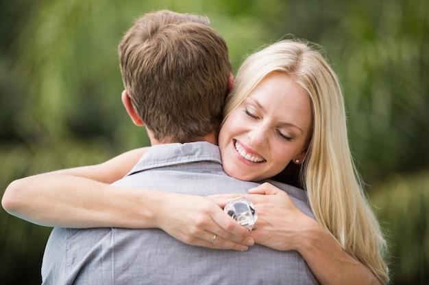 Giovane donna sorridente con gli occhi chiusi mentre abbraccia uomo
